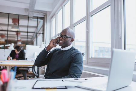 Photo for Young man talking on his mobile phone in office. African executive sitting at his desk with laptop - Royalty Free Image