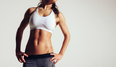 Close up of fit woman's torso with her hands on hips. Female with perfect abdomen muscles on grey background with copyspace.