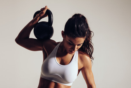 Foto de Determined young fitness woman exercising with kettle bell on grey background. Woman in sportswear doing crossfit workout with one hand. - Imagen libre de derechos