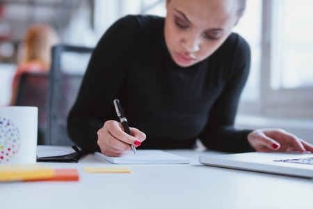 Photo pour Young woman working at her desk taking notes. Focus on hand writing on a notepad. - image libre de droit