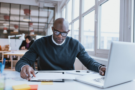 Foto de Young african executive sitting at his desk with laptop reading a document. African man working in office. - Imagen libre de derechos