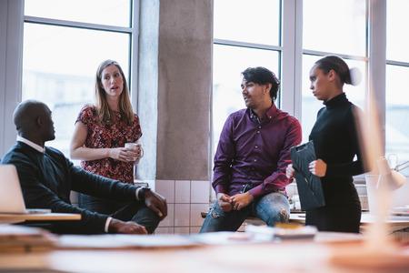 Foto de Shot of diverse business team discussing work in office. Creative young people discussing new business project. - Imagen libre de derechos