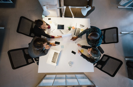 Foto de Office workers gather around a table to do research and implement new ideas. High angle view of multi-ethnic business people discussing in board room meeting - Imagen libre de derechos