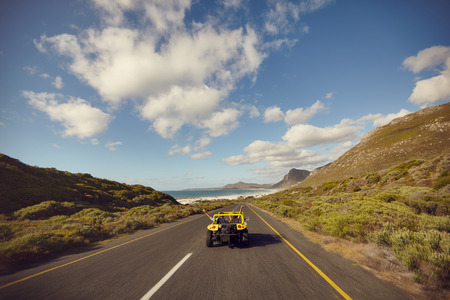 Photo pour Rear view shot of a young couple driving down an open road excited to be on a roadtrip. Happy couple driving a buddy car with their arms raised an a summer day. - image libre de droit