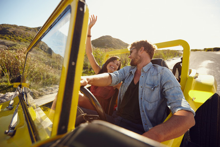 Foto de Beautiful young couple having fun on road trip. Man driving beach buggy on summer day with his girlfriend. - Imagen libre de derechos