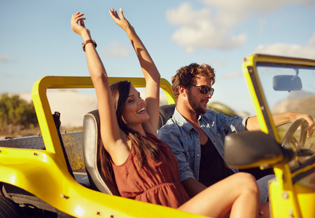 Photo pour Cheerful young couple driving in a car. Enjoying road trip. Young man driving car with woman enjoying the ride with her hands raised. - image libre de droit
