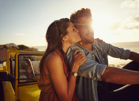 Photo for Romantic young couple sitting on the hood of their car while out on a roadtrip. Beautiful young woman kissing her boyfriend looking away smiling, outdoors. - Royalty Free Image