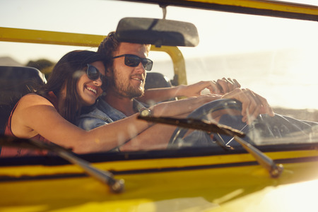 Foto de Portrait of romantic young couple going on a long drive in open car on a summer day. Handsome young man with his beautiful girlfriend on a road trip. - Imagen libre de derechos