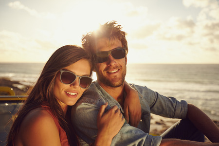 Photo pour Portrait of beautiful young couple wearing sunglasses looking at camera while on a road trip. Young man and woman with beach in background. - image libre de droit