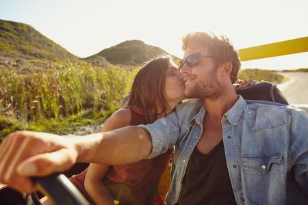 Photo pour Woman kissing her boyfriend driving a car. Lovely young couple on road trip. Affectionate caucasian couple enjoying road trip. - image libre de droit