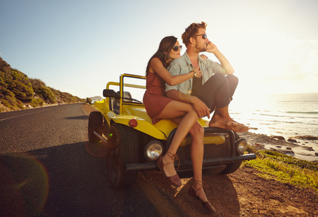 Photo pour Relaxed young couple sitting on the hood of their car alongside a open coastal road with man answering a phone call and woman sitting by. Young couple on road trip. - image libre de droit