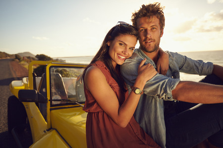 Photo pour Cheerful young couple sitting on the hood of their car while out on a roadtrip. Beautiful young couple together on a holiday, outdoors. - image libre de droit