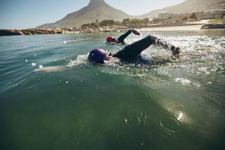 Photo pour Triathlon swimmers churning up the water. Athletes practicing for triathletic race in lake. - image libre de droit