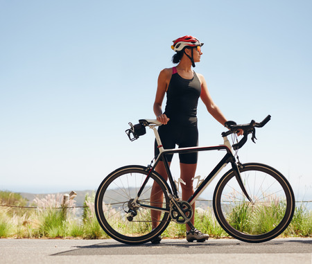 Foto de Full length image of young female cyclist looking away. Fit young woman wearing sportswear standing with her bicycle. - Imagen libre de derechos