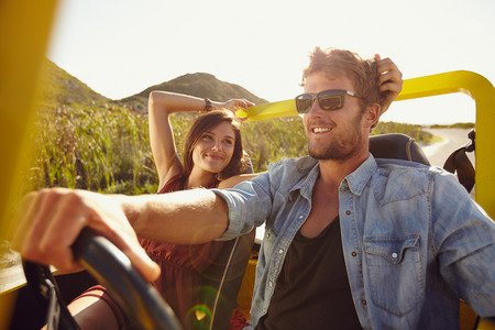 Photo pour Woman looking at man driving buggy car on a summer day. Loving young couple on road trip. - image libre de droit