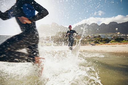 Foto de Image of triathletes rushing into the water. Athlete running into the water, training for a triathlon. - Imagen libre de derechos
