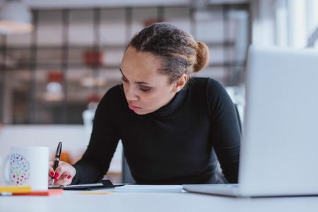 Foto de Portrait of young woman working at her desk. Busy african woman taking notes. - Imagen libre de derechos