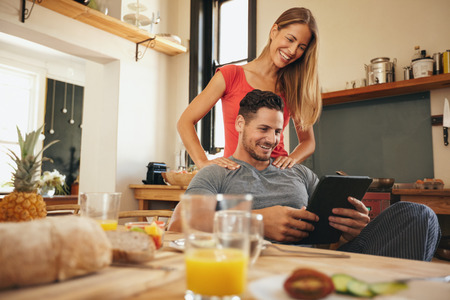 Photo pour Shot of happy young man and woman using digital tablet in morning. Couple using touchpad in kitchen smiling. - image libre de droit