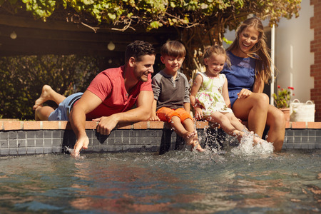 Caucasian family having fun by their swimming pool. Happy young family splashing water with hands and legs while sitting on edge of swimming pool. Kids with parents playing outdoors.