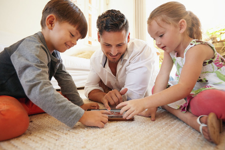Photo pour Father with son and daughter sitting on floor using digital tablet indoors. Happy young family together at home using touchpad computer. Young man teaching his children how to use digital tablet. - image libre de droit