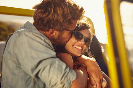 Foto de Young man embracing and kissing his beautiful girlfriend while on a road trip. Romantic couple in a car on summer holiday. - Imagen libre de derechos