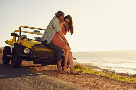 Photo pour Romantic young couple sharing a special moment while outdoors. Young couple in love on a road trip. Couple embracing each other while sitting on hood of their car in nature. - image libre de droit