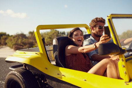 Foto de Excited happy couple enjoying road trip in their car. Man driving the car young woman taking a selfie from her mobile phone. - Imagen libre de derechos