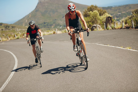 Foto de Cyclist riding bikes on open road. Triathletes cycling down the hill on bicycles. Practicing for triathlon race on country road. - Imagen libre de derechos