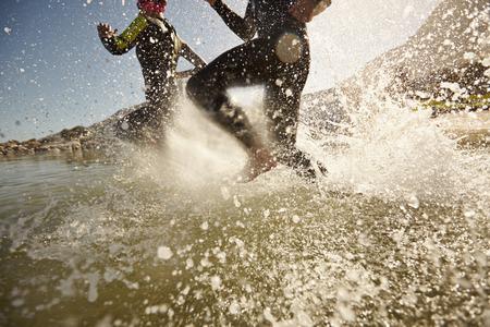 Photo pour Two triathlon participants running into the water for swim portion of race. Splash of water and athletes running. Focus on water splash. - image libre de droit