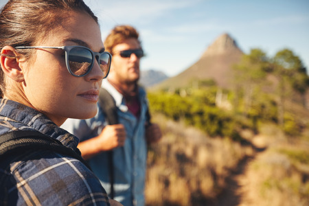 Foto de Close up image of young woman wearing sunglasses looking away with young man in background. Caucasian couple hiking in countryside. - Imagen libre de derechos