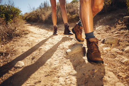 Photo pour Close-up of legs of young hikers walking on the country path. Young couple trail waking. Focus on hiking shoes. - image libre de droit