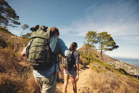 Foto de Rear view of two young people walking down the trail path on mountain. Young couple hiking with backpacks. - Imagen libre de derechos