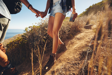 Foto de Close-up shot of young couple on a hiking trip. Cropped image of young man and woman hikers holding hands while walking on mountain trail. - Imagen libre de derechos