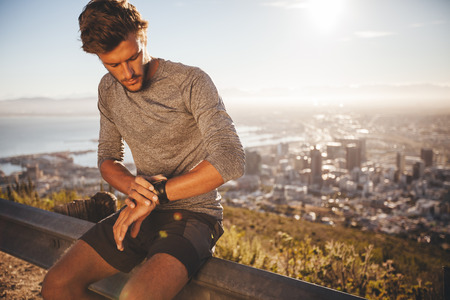 Foto de Young man adjusting his GPS watch before a run. Fit young athlete sitting on road railing and checking his watch while out for a run in morning. - Imagen libre de derechos