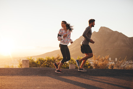 Photo pour Young couple jogging early in morning, with woman looking back over her shoulder. Young man and woman running outdoors on a country road. - image libre de droit