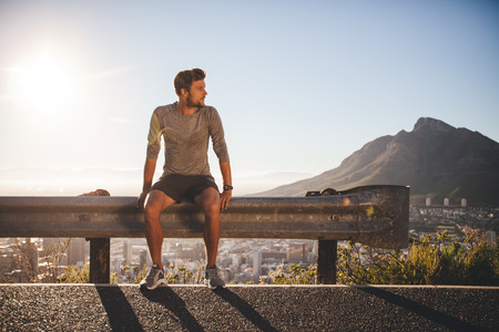 Photo for Male runner sitting on a guardrail on country road looking away on sunny day. Young man taking a break after morning run outdoors with bright sunlight. - Royalty Free Image