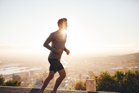 Foto de Young man training in the nature with sun behind him. Young man on morning run outdoors. - Imagen libre de derechos
