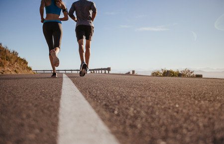 Photo for Rear view cropped shot of two young people running together on road. Man and woman on morning run on summer day. Low angle shot of couple jogging outdoors. - Royalty Free Image