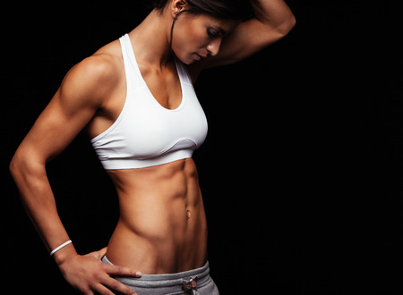 Foto per Cropped shot of fit woman's torso with her hands on hips. Female with perfect abdomen muscles posing on black background. - Immagine Royalty Free