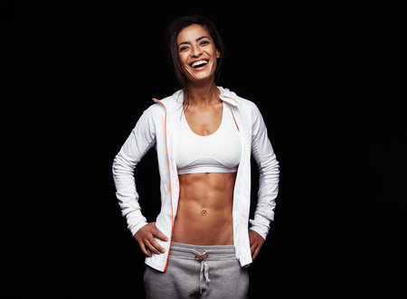 Photo for Smiling sportswoman in sportswear on black background. Caucasian fitness model looking happy with her hands on hips. - Royalty Free Image