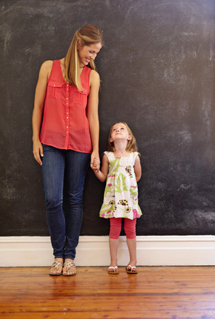 Foto de Full length shot of sweet little girl standing with her mother at home. Mother and daughter looking at each other against a wall, indoors. - Imagen libre de derechos