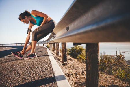 Photo pour Sports woman stretching her leg after running outdoors. Female athlete taking break after running training sitting on highway guardrail. - image libre de droit