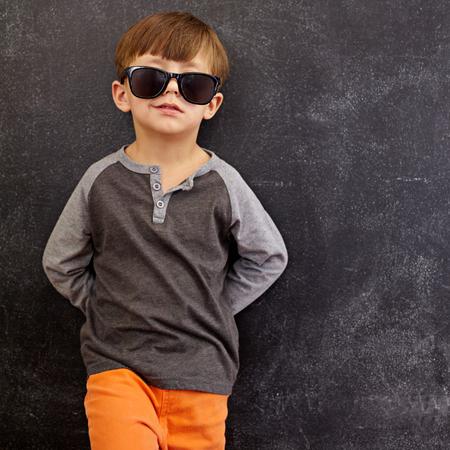 Foto de Portrait of smart little boy wearing sunglasses smirking. Cool kid in shades leaning on a blackboard looking at camera smiling with copy space. - Imagen libre de derechos