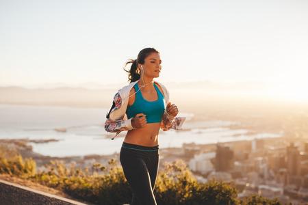 Foto de Fit young woman jogging outdoors. Female athlete on morning run with bright light. - Imagen libre de derechos