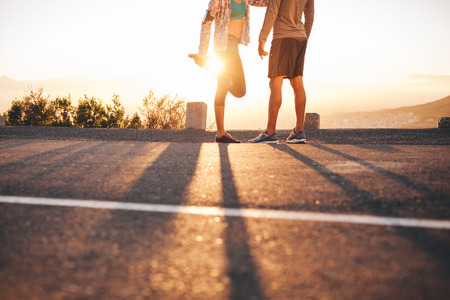 Foto de Cropped shot of fit young couple warming up before a run together at sunrise. Young man and woman exercising in morning. - Imagen libre de derechos