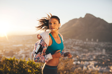 Foto per Female runner running outdoor in nature. Young woman jogging in morning looking over shoulder. - Immagine Royalty Free