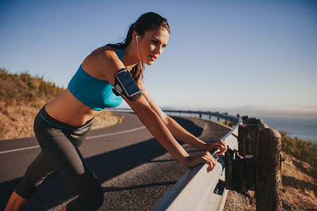 Photo for Young female athlete leaning on highway guardrail looking away. Woman runner outdoors on country road taking a break after running exercise. - Royalty Free Image