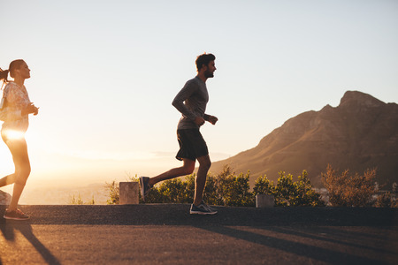 Foto de Outdoor shot of young couple on morning run. Young man and woman jogging on road outside during sunrise. - Imagen libre de derechos