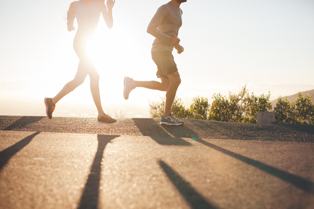 Foto de Low angle view of two people running on country road at sunrise. Cropped shot of young man and woman jogging in morning, with bright sunlight. - Imagen libre de derechos