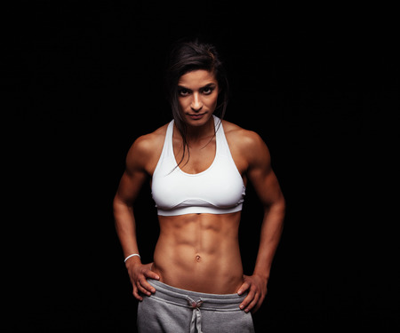 Foto de Shot of a strong woman with muscular abdomen in sportswear. Fitness female model posing on black background. - Imagen libre de derechos